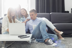 Happy parents with daughters using laptop in living room Stock Image