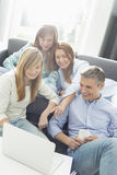 Happy parents with daughters using laptop in living room Royalty Free Stock Image