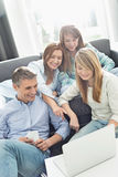 Happy parents with daughters using laptop in living room Royalty Free Stock Images