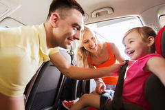 Happy parents fastening child with car seat belt Stock Photography