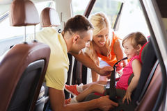 Happy parents fastening child with car seat belt. Family, transport, road trip and people concept - happy parents fastening child with safety belt in baby car royalty free stock photo