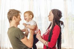 Happy parents father and mother playing with baby son at the in the morning on window background. Cheerful young family royalty free stock images