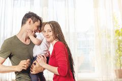 Happy parents father and mother playing with baby son at the in the morning on window background. Cheerful young family royalty free stock photography