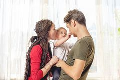 Happy parents father and mother playing with baby son at the on window background. Cheerful and modern young family stock photography