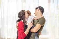 Happy parents father and mother playing with baby son at the on window background. Cheerful and modern young family stock image