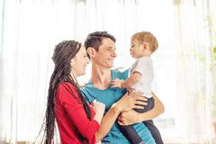 Happy parents father and mother playing with baby son at the on window background. Cheerful and modern young family stock photos