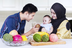 Happy parents give fruit to their child Royalty Free Stock Photo