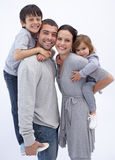 Happy parents giving children piggyback rides Stock Images