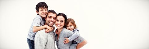 Happy parents giving children piggyback rides royalty free stock images