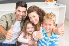 Happy parents giving thumbs up with their young children Stock Photo