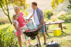 Happy parents grilling meat with daughter Royalty Free Stock Photo