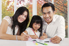 Happy parents help their child studying Royalty Free Stock Photos