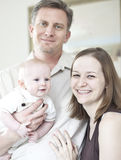 Happy parents holding baby. Portrait of happy parents holding 4 month old baby Royalty Free Stock Images