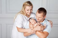 Happy parents holding a cute newborn girl. Mom, dad and baby. Cl royalty free stock photos