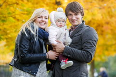 Happy parents holding daughter on arms in autumn park Royalty Free Stock Images