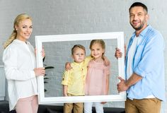 happy parents holding frame and cute little children stock photos