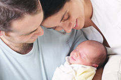 Happy parents holding their newborn baby Stock Images