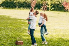 happy parents hugging adorable kids at picnic stock images