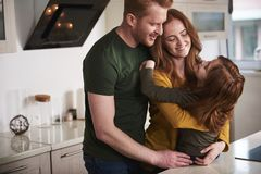 Happy parents hugging daughter in kitchen stock images