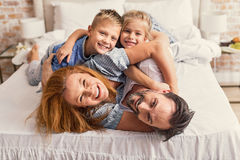 Happy parents and kids enjoying their morning in bed Stock Photo