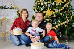 Happy parents and kids with gifts near Christmas tree at home. Family concept. stock photography