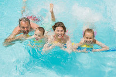 Happy parents and kids having fun in pool Royalty Free Stock Photos