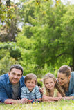 Happy parents and kids lying at park Royalty Free Stock Photography