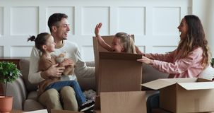 Happy parents and kids playing on moving day unpacking boxes