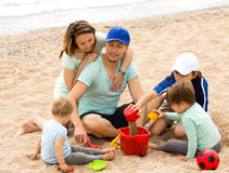 Happy parents and kids playing with sand. At sea shore Stock Images