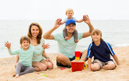 Happy parents with kids sitting at sandy beach Royalty Free Stock Photo