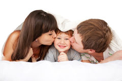 Happy parents kissing child in bed Royalty Free Stock Photos