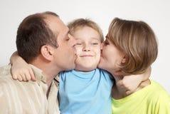 Happy parents kissing son stock photos