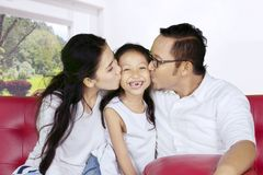 Happy parents kissing their daughter at home Stock Photo