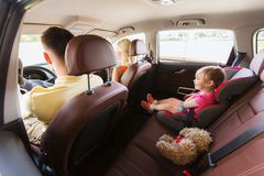 Happy parents with little child driving in car stock photo