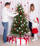 Happy parents and little daughter decorating Christmas tree at h Royalty Free Stock Photo