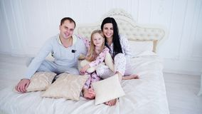 Happy parents and little daughter sitting on bed in morning, wearing pajamas. stock photos