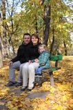 Happy parents and little girl. Portrait with happy parents and little girl sitting on a bench in the park Stock Photos