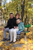 Happy parents and little girl. Portrait with happy parents and little girl sitting on a bench in the park Royalty Free Stock Images