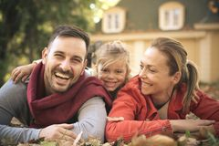 Happy parents with little girl laying on ground, poses to camera royalty free stock photography
