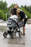 Happy parents look at the baby. Happy parents look at the baby in a perambulator Royalty Free Stock Photography
