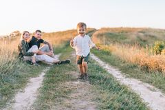 happy parents looking at adorable smiling little son running stock photography