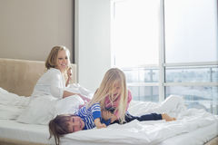 Happy parents looking at playful children in bedroom Royalty Free Stock Images
