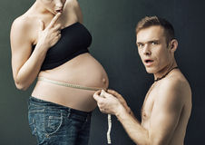 Happy parents measuring on pregnant woman's belly royalty free stock photography