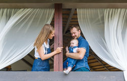 Happy parents play with the little son on a balcony.  Royalty Free Stock Photo