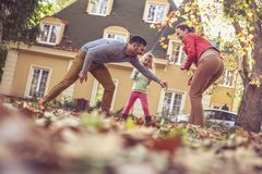Happy parents playing with daughter. Autumn season. On the move. stock photography