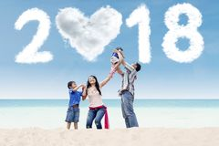 Happy parents with children and numbers 2018 Stock Photo