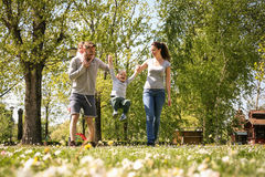 Happy parents playing with their children in the meadow. Family royalty free stock photos