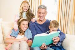 Happy parents reading to their kids Stock Photos