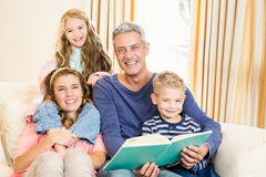 Happy parents reading to their kids Stock Images