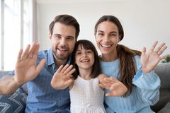 Smiling family with little kid waving talking on webcam royalty free stock photography